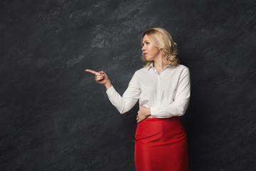 Serious businesswoman pointing away