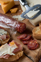 bread, meat, and cheese platter assortment on wood board