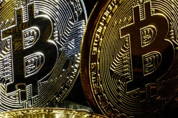 Golden bitcoins on a black computer keyboard