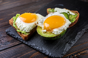 Avocado and egg  toast on a rustic wooden background