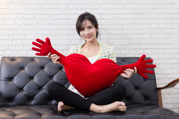 pretty asian woman play with red heart dool on sofa