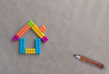 House concept with plastic blocks toy and wooden handle pencil on leather floor