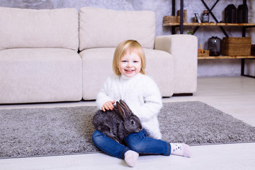 Cute little girl with grey Easter rabbit, bunny. Blonde baby girl smiling in white sweater and blue jeans sitting at home on the carpet near the sofa..