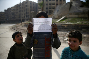 """Children hold a warning leaflet dropped by plane entitled """"Keep yourself and your family aware"""" in the besieged town of Douma"""