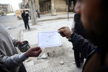 """People hold a warning leaflet dropped by plane entitled """"Keep yourself and your family aware"""" in the besieged town of Douma"""