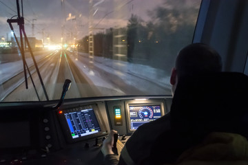 View from the driver's cab of an electric train, a night voyage on a railway.