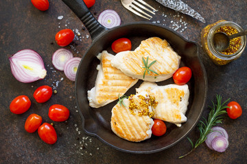 Grilled chicken fillet on a cast-iron frying pan, dark stone or slate background, top view flat lay background.