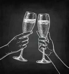 Two hands clinking glasses of champagne.