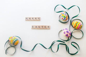 Bright Easter egg tied by green ribbon on white background