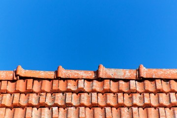 An old roof with burnt tiles. Roof in village house against a blue sky background.