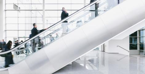 Fototapete - crowd of blurred business people rushing on escalators