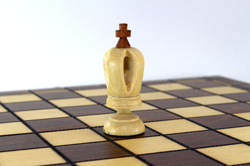 Lone chess white king on a chessboard on white background close-up