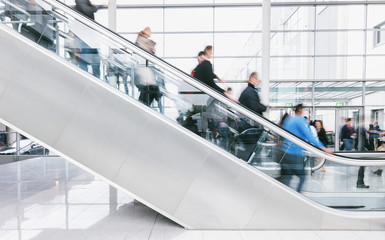 crowd of blurred people rushing on escalators at a trade fair hall