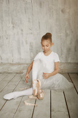 A little adorable young ballerina in white dress wearing her point shoes sitting on woody floor and...