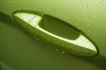 closeup of raindrops on handle of green car