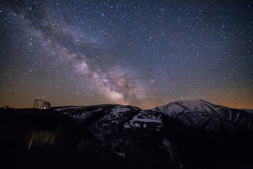Starry sky with milky way over Caucasian mountains and observatory