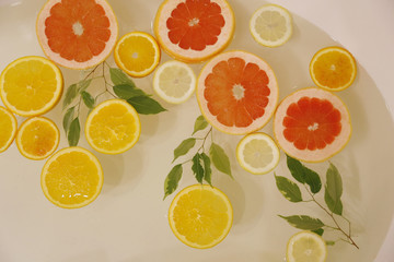 slices of citrus yellow lemon, orange and red grapefruit in the water of bath