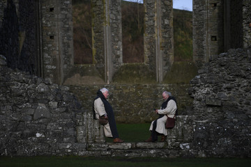 Actors from the Magnus Viking Association playing Monks look at an iPad during the re-enactment of the landing of Saint Patrick in Ireland at Inch Abbey in Downpatrick