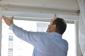 Man installing a new white blind on a window