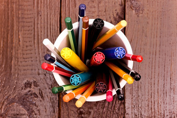 Still life, business, education concept. Crayons and markers in a Cup on a wooden table. Top view, copy space background.