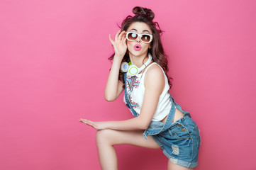 Pretty fashion cool smiling girl with headphones knitted bag sunglasses wearing a colorful clothes with curly hair dancing happy over pink background. Beauty Lifestyle Teenager People Music concept