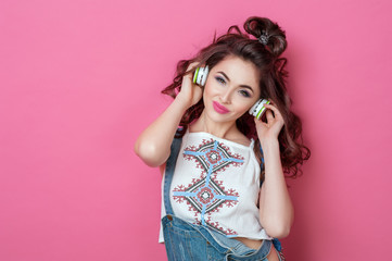 Pretty fashion cool smiling girl listening to music in headphones wearing a colorful clothes with curly hair over pink background. Beauty Lifestyle Teenager People Music concept