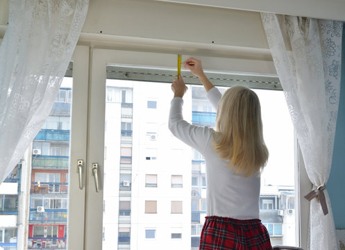Blonde woman measuring and marking a position of a hole in order to install a blind. Residential building is in a background