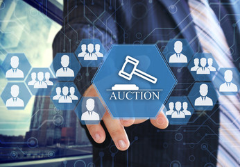 The businessman chooses auctions  button on the touch screen with a futuristic background .The concept  online auctions .