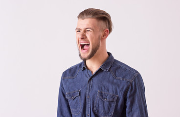 Portrait of aggressive bearded hipster shouting while isolated on white background. Young stylish man screaming loudly, expressing his negative emotions. Furious student with widely open mouth