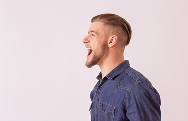 Side view happy, stylish hipster man screaming loudly while isolated on white background with copyspace. Happy bearded man shouting and smiling against white background. Expressing positive emotions
