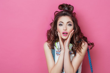Surprised Pretty fashion cool girl with headphones wearing colorful clothes with curly hair looks isolated over pink background. Beauty Lifestyle Teenager People Emotions