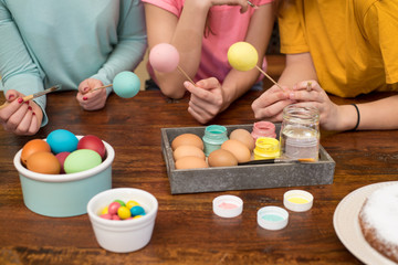 Young girls are painting Easter eggs