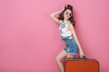 Happy beauty woman traveler holding a vintage suitcase on road. Fashion People Lifestyle Travel concepts. Cute glamour girl in sunglasses with curly hair posing in studio.