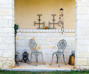 limestone patio with 2 wrought iron chairs and artistic accessories