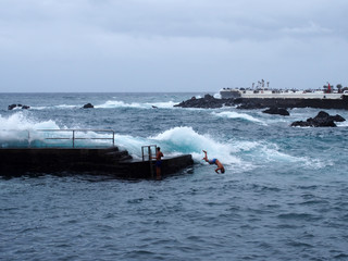 young man jumping of a concrete pier into the sea with high waves and white surf in puerto de la cruz tenerife