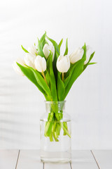 Bouquet of white tulips in glass vase on the white wooden table