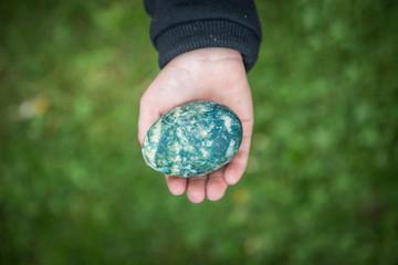 Easter egg in little boy hand over green gras