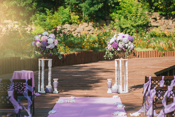 Wedding arch in a summer garden on a terrace of vintage white pedestals with purple bouquets of flowers hydrangea