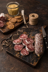 Spicy salami is service with mustard and seeded crackers