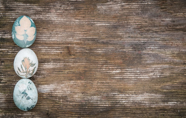 Three Easter eggs over rustic wood with copy space, holiday background
