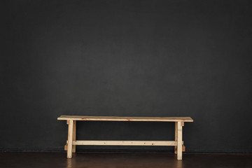 Wooden bench in a room with a black wall