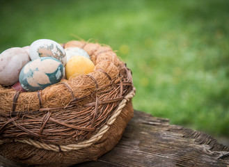 Basket with natural colored Easter eggs over green grass background and space for text