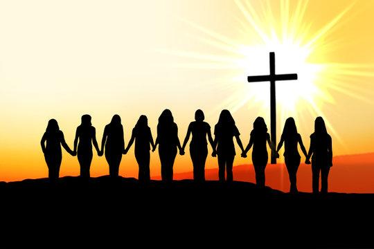 Christian women friendship silhouette walking towards the cross in the light.