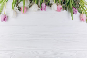 Violet and white tulips on a wooden background.
