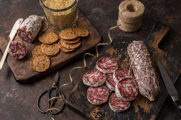 Hot and spicy salamis are paired with crackers and spicy mustard for the perfect appetizer