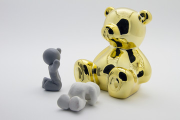 Clay characters pray to golden bear, on white background