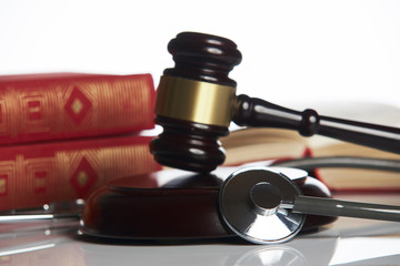 Medicine law concept. Law books with wooden judges gavel and medical stethoscope on white table in a courtroom or enforcement office, close-up. selective focus