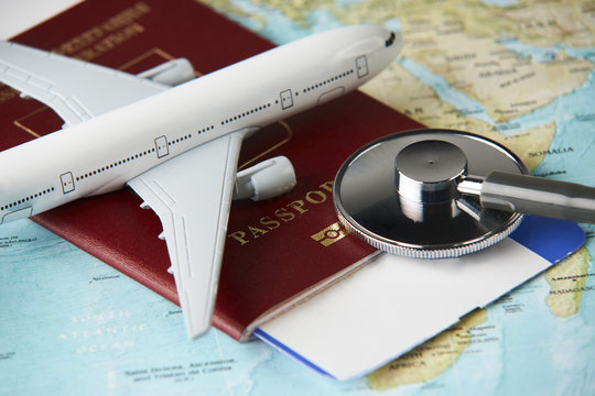 Boarding pass and a passport travel documents with medical stethoscope and airplane on world map background, close-up. Medical travel concept