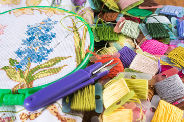 The process of cross-stitch. Canvas on hoops, needles, embroidery floss and pattern.