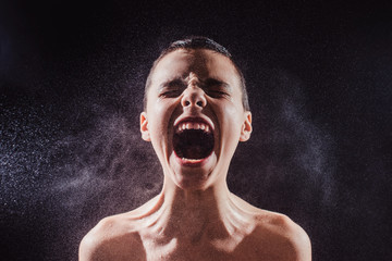 Young boy yelling in the spray of water on a black background.